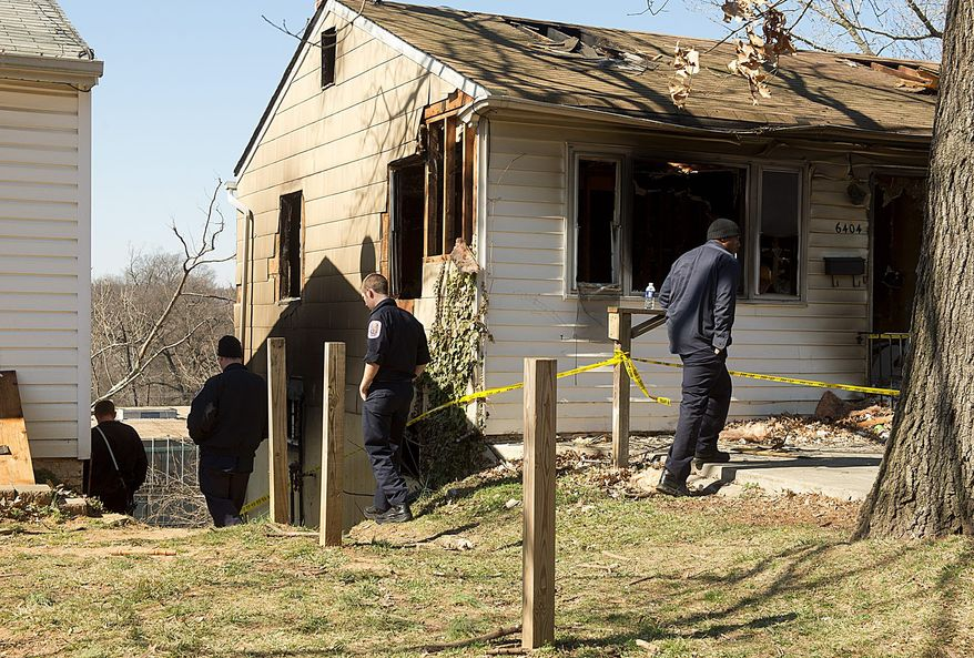 Firefighters with the Landover Hills Fire Department check out a fire-damaged house from a February 2012 arson in Riverdale, where two firefighters with the Bladensburg Volunteer Fire Department suffered serious burns. (Barbara L. Salisbury/The Washington Times)