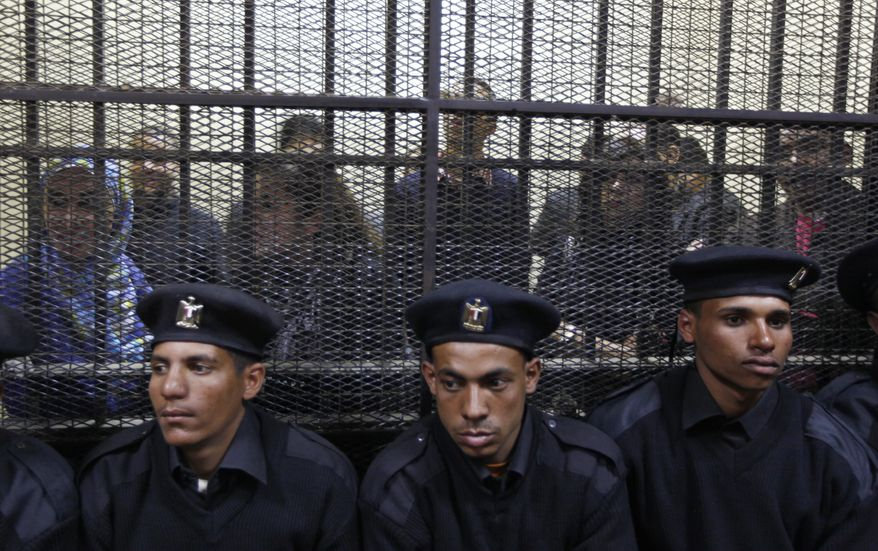 Policemen in a Cairo courtroom on Sunday, Feb. 26, 2012, sit in front of Egyptian employees of several pro-democracy groups charged with using foreign funds to foment unrest. The trial of 16 Americans and 27 others has plunged relations with the U.S. into the deepest crisis in decades. (AP Photo/Khalil Hamra)