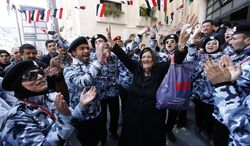 A Syrian woman (center) dances between pro-Syrian-regime supporters wearing police uniforms as they celebrate outside a polling station during a referendum on the new constitution in Damascus, Syria, on Sunday, Feb. 26, 2012. (AP Photo/Muzaffar Salman)
