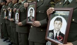 Police officers in Bogota, Columbia, on Thursday Feb. 23, 2012, hold photographs of fellow officers who were kidnapped by rebels of the Revolutionary Armed Forces of Colombia (FARC). (AP Photo/Fernando Vergara)
