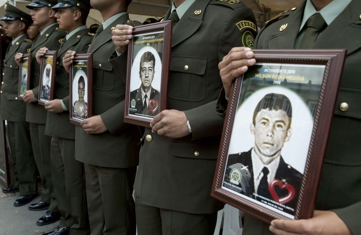 Police officers in Bogota, Columbia, on Thursday Feb. 23, 2012, hold photographs of fellow officers who were kidnapped by rebels of the Revolutionary Armed Forces of Colombia (FARC