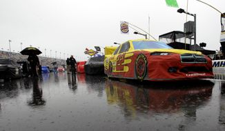 AJ Allmendinger's car (22) and others remain parked on pit road due to a rain delay before the start of the Daytona 500 at Daytona International Speedway in Daytona Beach, Fla., Sunday, Feb. 26, 2012. The race was postponed until Monday. (AP Photo/John Raoux)