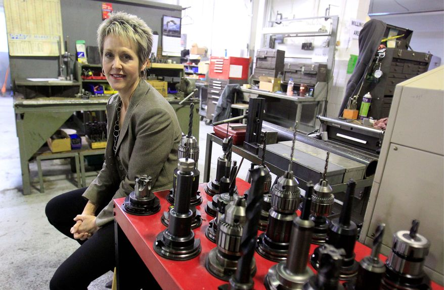 In this Feb. 8, 2012 photo, Laurie Schmald Moncrieff president of Schmald Tool and Die in Burton, Mich., sits in her shop. Moncrieff says she began shifting from autos to the green energy, aerospace and defense industries when demand collapsed. (AP Photo/Carlos Osorio)