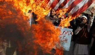 Pakistani protesters burn representations of U.S. flags in Lahore on Monday to condemn the reported burning of Korans in Afghanistan by U.S. troops. Afghan President Hamid Karzai has urged calm, calling on his countrymen not to allow insurgents to capitalize on their indignation to spark violence.