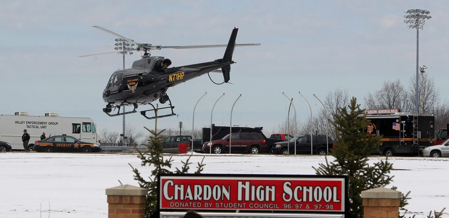 An Ohio State Highway patrol helicopter leaves Chardon High School in Chardon, Ohio, on Monday after a gunman opened fire inside the high school's cafeteria at the start of the school day. One student was killed, and four were wounded by the shooter. A suspect was captured and is in custody. (Associated Press)