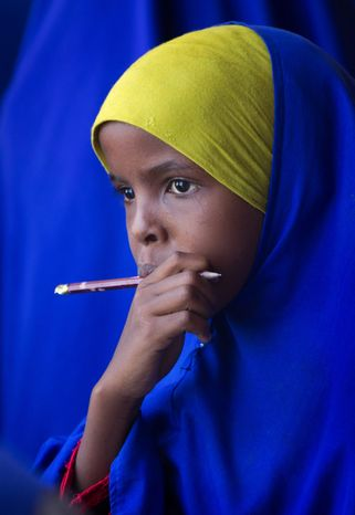 A Somali schoolgirl watches the arrival of Kenyan soldiers and media in the town of Dhobley, currently under the control of Kenyan military and Somali government forces. Stabilization will be an even bigger task than chasing out militants, officials say. (Associated Press)