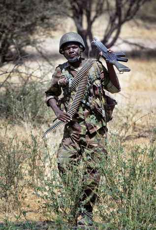 "Kenyan soldier Nicholas Munyanya wears a helmet with the words written in Kiswahili ""Tea in Kismayo,"" a referen"