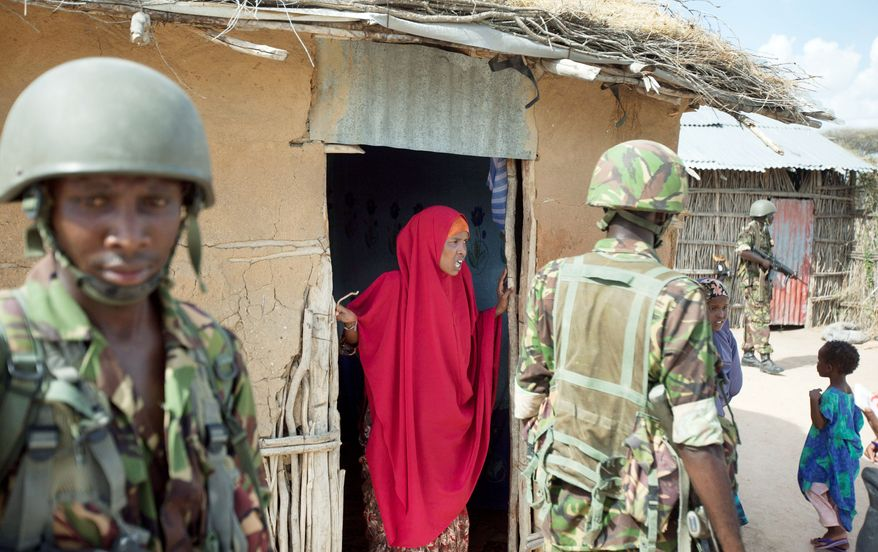 A Somali villager talks to Kenyan soldiers, who crossed the border after abductions and grenade attacks inside Kenya were linked to the al Qaeda-linked al-Shabab in Somalia. (Associated Press)