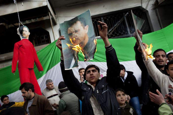 People burn portraits of Syrian President Bashar Al-Assad during a Feb. 26, 2012, demonstration against his regime in the outskirts from Idlib in northern Syria. (Associated Press)