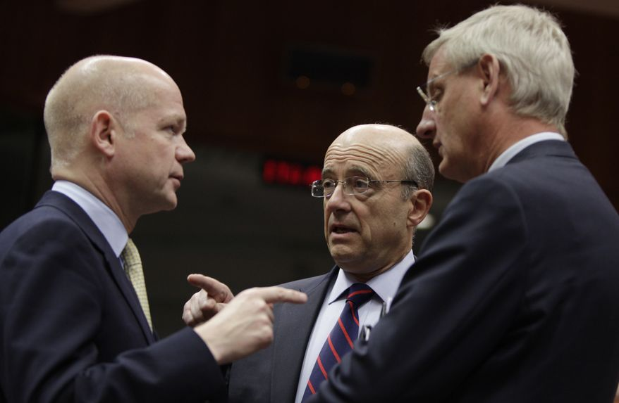 British Foreign Minister William Hague (left) speaks Feb. 27, 2012, with French Foreign Minister Alain Juppe (center) and Swedish Foreign Minister Carl Bildt during a meeting of EU foreign ministers at the EU Council building in Brussels. (Associated Press)