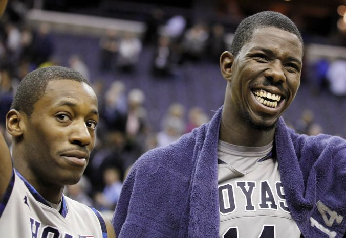"""Georgetown's Jason Clark, left, and Henry Sims smile as they are acknowledged by the crowd for their combined for 25 points, 12 rebounds and six assists on """"Senior Day,"""" following their game against Notre Dame, Monday, Feb. 27, 2012, in Washington. Georgetown won 59-41. (AP Photo/Haraz N. Ghanbari)"""