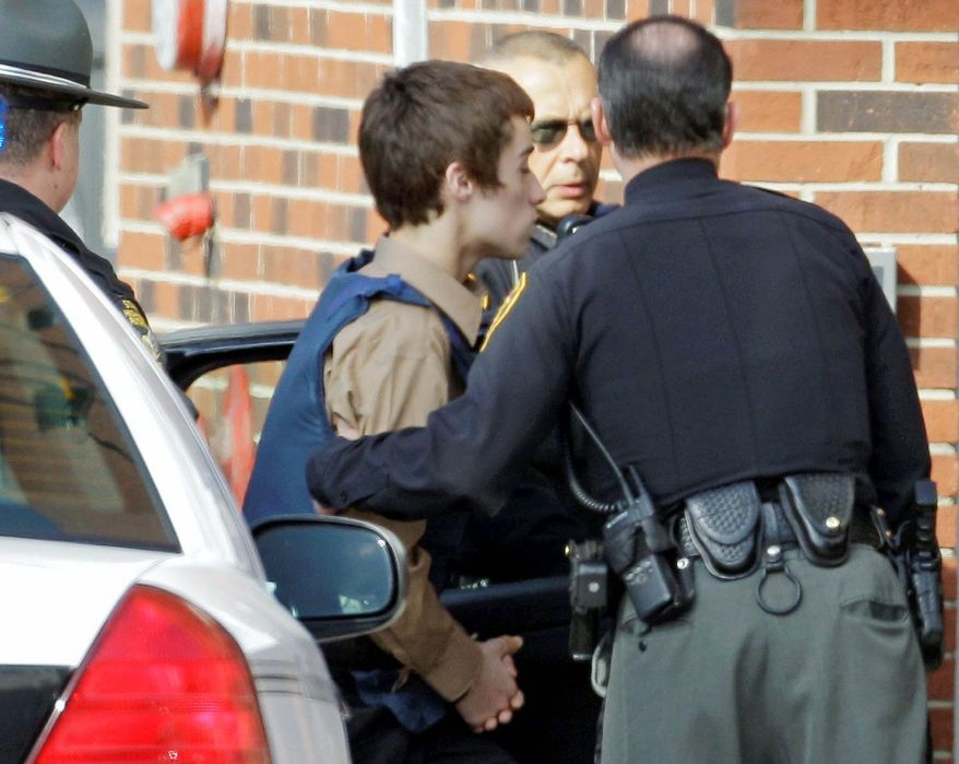T.J. Lane, a suspect in Monday's shooting of five students at Chardon High School, is taken into juvenile court by Geauga County deputies in Chardon, Ohio, on Tuesday. Three of the five students wounded in the attacks have since died. (Associated Press)