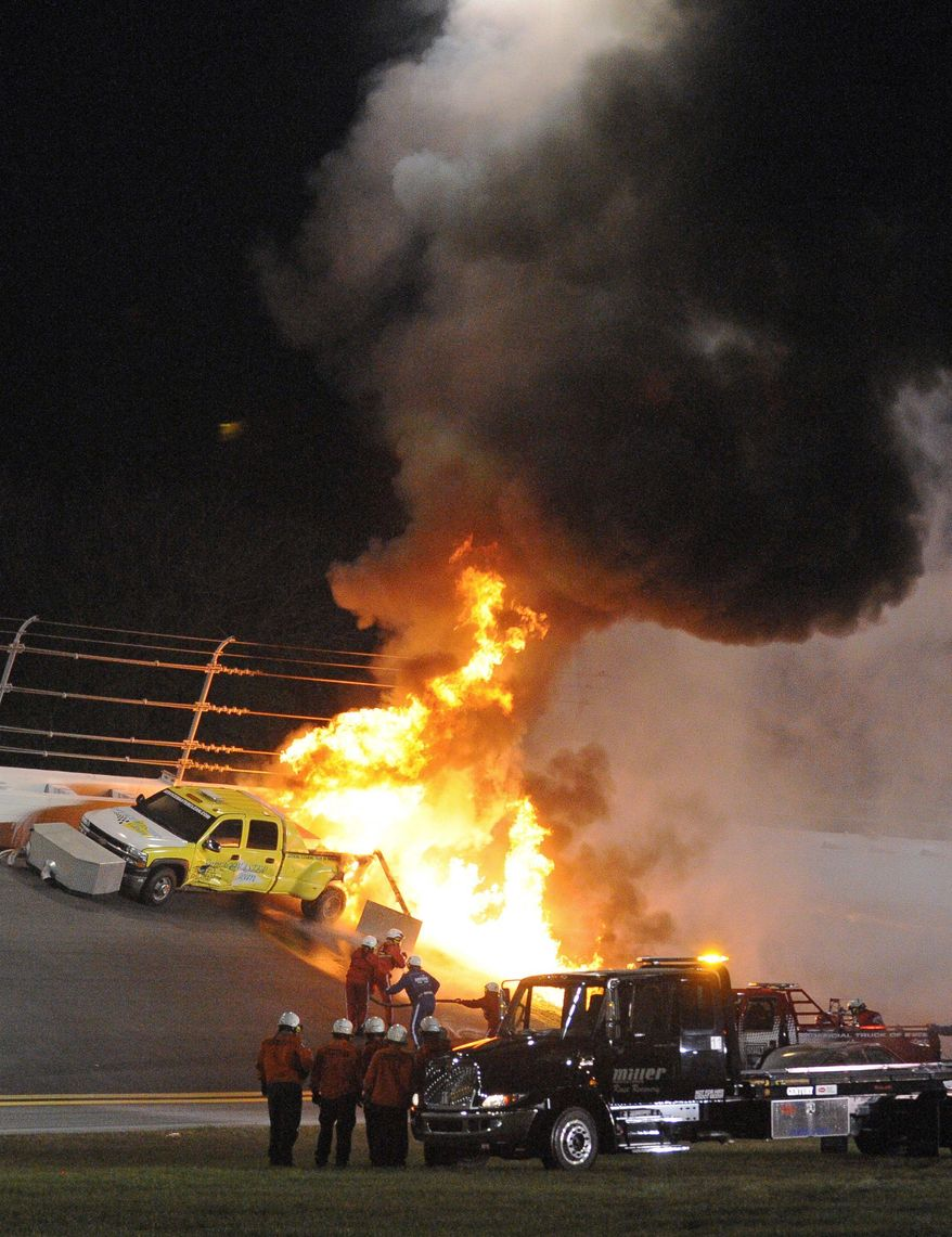Emergency workers try to extinguish a fire on a jet dryer during the Daytona 500 on Monday. Juan Pablo Montoya's car struck the dryer during a caution period after something on his car broke, igniting the fuel on the truck. (Associated Press)