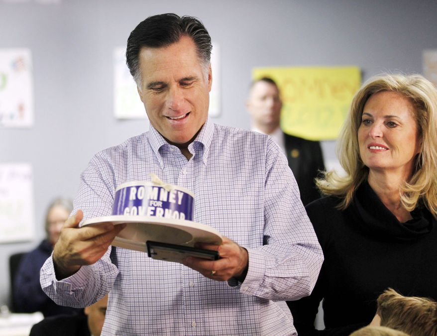 GOP presidential hopeful Mitt Romney admires a souvenir Tuesday in Livonia, Mich. It was from his father's Michigan gubernatorial campaign in the 1960s that was being worn by one of his own volunteers who also worked on his father's campaign. (Associated Press)