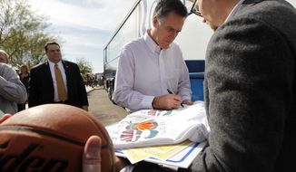 ** FILE ** Republican presidential candidate, former Massachusetts Gov. Mitt Romney signs autographs outside his campaign bus after a campaign rally at Tri-City Christian Academy in Chandler, Ariz., Wednesday, Feb. 22, 2012. (AP Photo/Gerald Herbert)