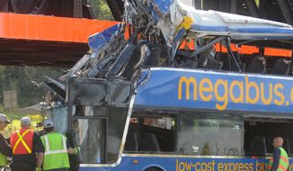 **FILE** Investigators examine the driver's area of the bus at the scene of a fatal double-decker Megabus accident just outside Syracuse, N.Y., on Sept. 11, 2010. The bus hit the Onondaga Lake Parkway railroad bridge abutment and rolled onto its side, killing four passengers. (Associated Press/The Post-Standard)