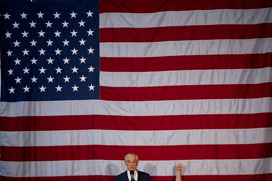 A veteran sitting onstage behind Rep. Ron Paul, a GOP presidential candidate, raises a fist of support as Mr. Paul delivers a speech highlighting veterans at the Iowa State Fairgrounds in Des Moines, Iowa, on Wednesday, Dec. 28, 2011. (Andrew Harnik/The Washington Times)
