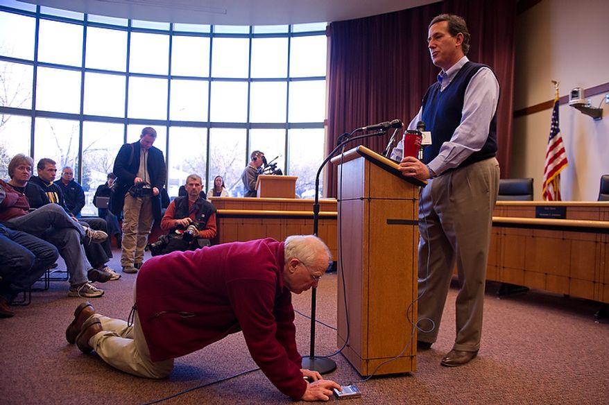 "A man checks his voice recorder as Republican presidential candidate Rick Santorum speaks on ""faith, family and freedom"" at a town-hall meeting on Thursday, Dec. 29, 2011, at City Hall in Coralville, Iowa. (Andrew Harnik/The Washington Times)"