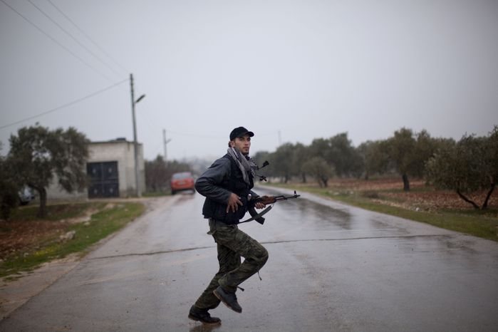 A Free Syrian Army fighter runs as Syrian government troops advance toward the town of Sarmin, in northern Syria, on Monday, Feb. 27, 2012. (AP Photo/Rodrigo Abd)