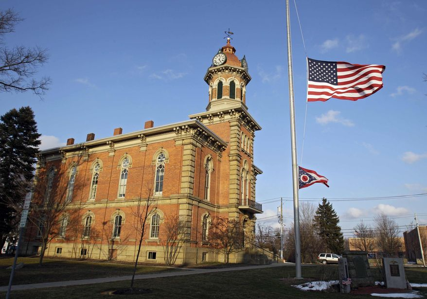 Flags fly at half-staff in front of the town hall in Chardon, Ohio, for the victims of an early-morning school shooting on Monday, Feb. 27, 2012. (AP Photo/Mark Duncan)