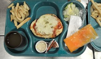 **FILE** A tray containing pizza, fries, salad, a frozen fruit desert and drink is prepared July 21, 2011, for a prisoner during lunch at the Bellamy Creek correctional facility near Ionia, Mich. (Associated Press/The Detroit News)