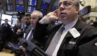 Trader Michael Iervoline (right) works on the floor of the New York Stock Exchange on Feb. 28, 2012. (Associated Press)