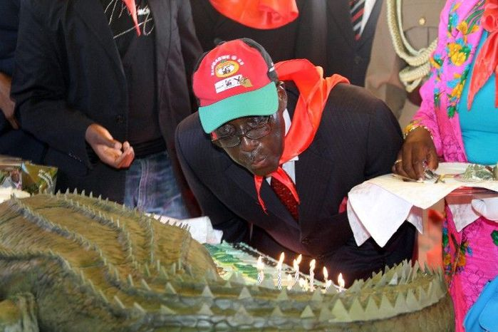 Zimbabwean President Robert Mugabe blows out the candles on his birthday cake as he turns 88. The cake was baked in Harare and transported to Mutare under police escort for an annual celebration targeted at Zimbabwean youths. (Associated Press)