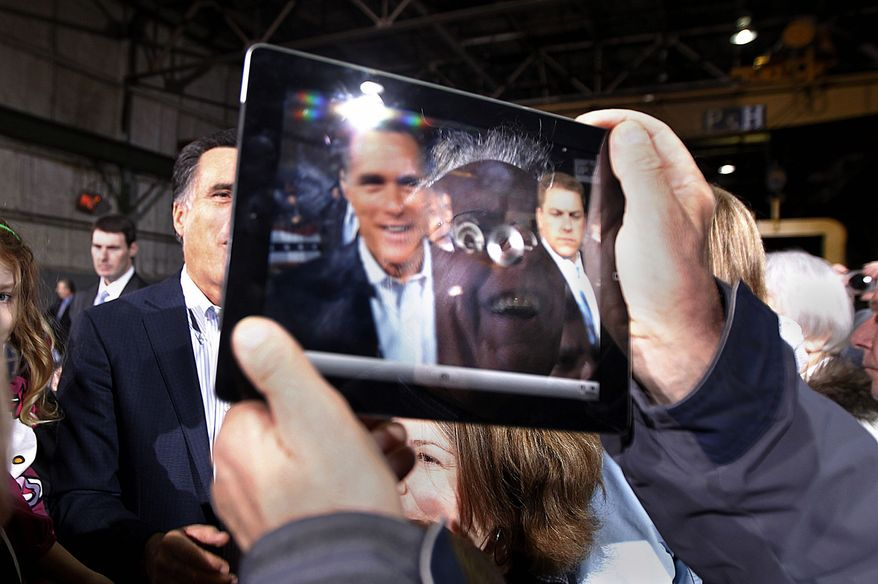 A supporter's reflection and the image of former Massachusetts Gov. Mitt Romney are seen on the screen of his iPad as he photographs Mr. Romney greeting supporters at American Posts in Toledo, Ohio, on Wednesday. (Associated Press)