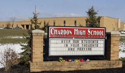 Bouquets of flowers sit on the sign in front of the high school in Chardon, Ohio, Tuesday, Feb. 28, 2012. A gunman opened fire inside the school's cafeteria at the start of the school day Monday. (AP Photo/Mark Duncan)