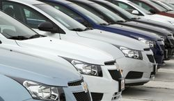 A long line of 2012 Cruze sedans sit at a Chevrolet dealership in the south Denver suburb of Englewood, Colo., on Sunday, Feb. 19, 2012. (AP Photo/David Zalubowski)