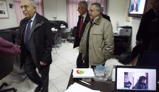 Palestinian Prime Minister Salam Fayyad (left) visits the offices of al-Watan TV after an Israeli army pre-dawn raid in the West Bank city of Ramallah on Feb. 29, 2012. A Palestinian broadcaster says Israeli troops raided his TV station, seizing transmission equipment, computers and documents. A computer screen on right shows an Israeli soldier during the raid. (Associated Press)