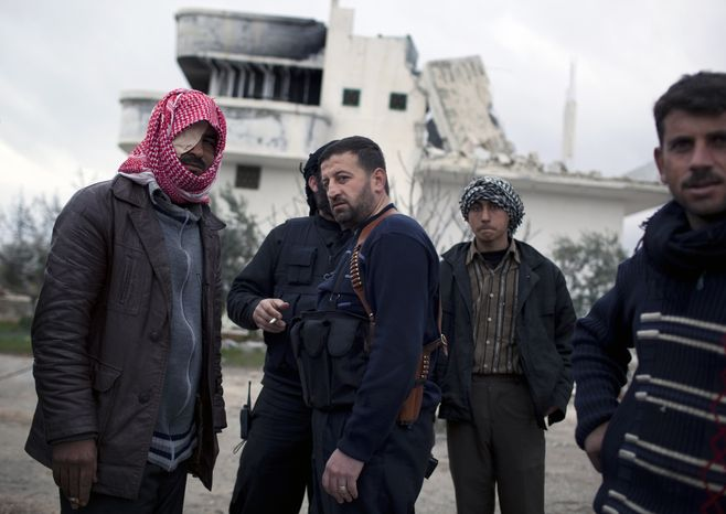 Free Syrian Army soldiers gather Feb. 28, 2012, outside a house destroyed in fighting against President Assad's forces in Sarmin, north Syria. (Associated Press)