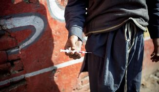 A drug addict holds a needle and syringe after injecting himself with heroin in Rawalpindi, Pakistan. Addicted street children are easy prey for militants.