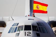 A Spanish flag is waved from a plane carrying some of the 17 tons of silver and gold coins scooped up from a Spanish warship, Nuestra Senora de las Mercedes, that sank during a 1804 gunbattle, after its arrival at the Torrejon De Ardoz military air base, near Madrid, on Saturday Feb. 25, 2012. (AP Photo/Daniel Ochoa de Olza)