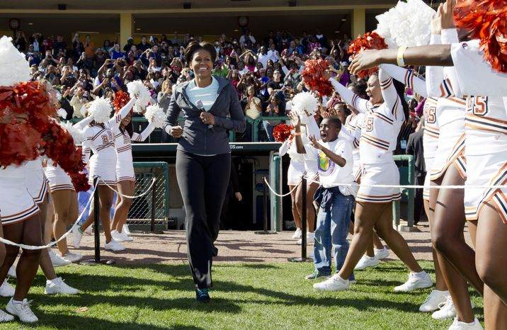 """** FILE ** First lady Michelle Obama runs onto the field as she arrives for physical activity with kids at the ESPN Wide World of Sports Complex at the Walt Disney World Resort in Orlando, Fla., on Saturday, Feb. 11, 2012 during her three-day national tour celebrating the second anniversary of the """"Let's Move"""" program fighting childhood obesity. (AP Photo/Carolyn Kaster)"""