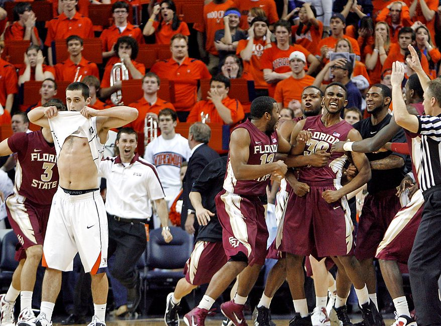 Virginia's Sammy Zeglinski, left, pulls his jersey to his face as Florida State's Ian Miller (30) celebrates with his teammates after sinking a 3-pointer in the final seconds to give Florida State a 63-60 victory in Charlottesville Va., Thursday, March 1, 2012. (AP Photo/Richmond Times-Dispatch, Mark Gormus)