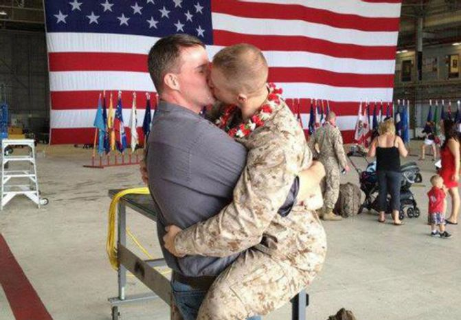 """Marine Corps Sgt. Brandon Morgan (right) greets his boyfriend with a passionate kiss at an on-base military-family homecoming. A friend photographed the embrace, which was posted on the """"Gay Marine"""" Facebook page. (Courtesy of Facebook)"""
