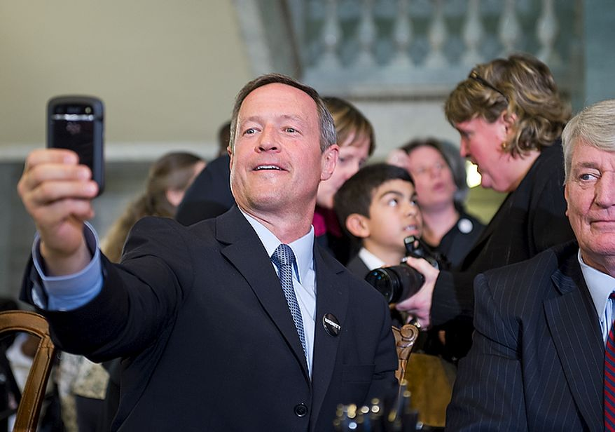 Maryland Gov. Martin O'Malley holds out a cell phone to take a picture after signing the Civil Marriage Protection Act into law at the Maryland State House in Annapolis, Md., on Thursday, March 1, 2012. (Barbara L. Salisbury/The Washington Times)
