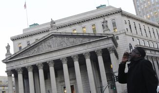 ** FILE ** A member of the Muslim community performs a call to prayer during a rally in New York on Feb. 3, 2012, to demand the resignation of police Commissioner Ray Kelly and police department spokesman Paul Browne. Thirty-three civil rights groups from around America complained to the New York attorney general about police documents that showed the New York Police Department recommending increased surveillance of Shiite mosques based solely on their religion. (Associated Press)
