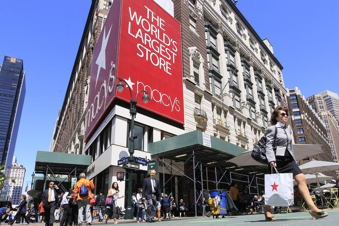 ** FILE ** Shoppers carrying Macy's bags walk past the chain's flagship store in New York in May 2011. (AP Photo/Mary Altaffer, File)