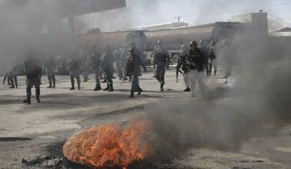 **FILE** Black smoke rises from tires which were burnt by protesters as Afghan policemen march during an anti-U.S. demonstration in Kabul, Afghanistan, on Feb. 22, 2012. (Associated Press)