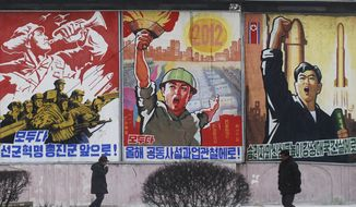 """**FILE** Residents walk Feb. 11, 2012, on a street in Pyongyang, North Korea, past posters with popular slogans illustrating North Korea's main policies. From left to right, they read, """"Let's march toward a military first revolution,"""" """"Let's accomplish the tasks laid out in this year's joint new year's editorial,"""" and """"Devote the victors' hearts to the building of a strong nation."""" (Associated Press)"""