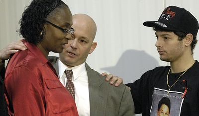 Ron Parmertor, uncle of Daniel Parmertor, center, and Daniel's brother Dominic, right, pause to comfort Phyllis Ferguson, mother of Demetrius Hewlin, Thursday, March 1, 2012, during a news conference in Eastlake, Ohio. Daniel Parmertor, Demetrius Hewlin and Russell King Jr. were killed by a gunman at Chardon High School Monday. (AP Photo/News-Herald, Maribeth Joeright)