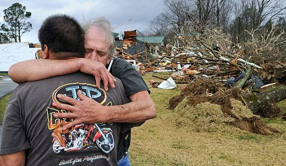 Greg Cook hugs his friend David Derrick at East Limestone community on Friday, March 2, 2012.  A reported tornado destroyed several houses in northern Alabama as storms threatened more twisters across the region Friday (AP Photo/The Decatur Daily, Gary Cosby Jr.)
