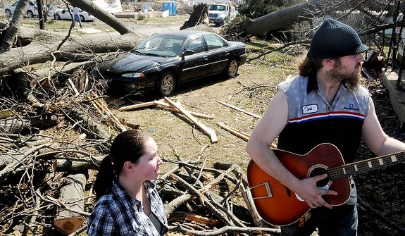 Levi Fogle strums on his guitar alongside Sarah Pearce outside their South Water Street home Thursday, March 1, in Harrisburg, Ill. (AP Photo/The Southern Illinoisan, Paul Newton)