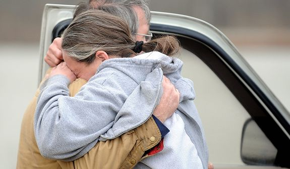 Judy Hudnall, right, buries her head in her brother, Gene Pickerill's arms after she arrived at the scene on Nugent Drive in Henderson, Ky Wednesday, Feb. 29, 2012. Waves of strong storms ripped roofs off homes, apartment buildings and a bank and destroyed several buildings in north-central Kentucky.  (AP Photo/The Gleaner, Darrin Phegley)