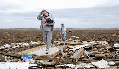Judy Hudnall sift through the debris left from Wednesday morning's storm in Henderson Ky. Wednesday, Feb. 29, 2012. Waves of strong storms ripped roofs off homes, apartment buildings and a bank and destroyed several buildings in north-central Kentucky.  (AP Photo/The Gleaner, Darrin Phegley)