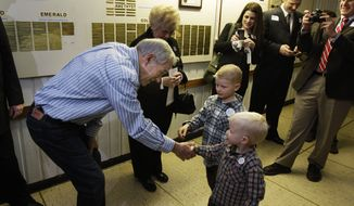 Republican presidential candidate Rep. Ron Paul, R-Texas, left, shakes hands with Henry Nichols, 3, foreground, and Davis Nichols, 6, as their father Jonathan Nichols takes their photo as Paul and his wife Carol, center, greet people taking part in Washington state caucus meetings, Saturday, March, 3, 2012, in Puyallup, Wash. (AP Photo/Ted S. Warren)