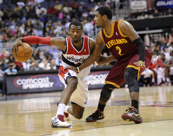 Washington Wizards guard John Wall dribbles against Cleveland Cavaliers guard Kyrie Irving during the second half Saturday, March 3, 2012, in Washingto