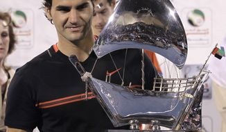 Roger Federer holds the winning trophy after defeating Andy Murray in the men's singles final at the Emirates Dubai ATP Tennis Championships in Dubai, United Arab Emirates, on Saturday, March 3, 2012. (AP Photo/Hassan Ammar)